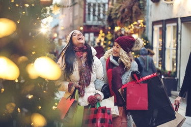 Photo of two women laughing and holding many shopping bags in a street decorated with Christmas trees and lights