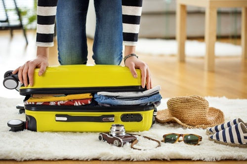 Woman packing for a trip is trying to close her over filled yellow suitcase.