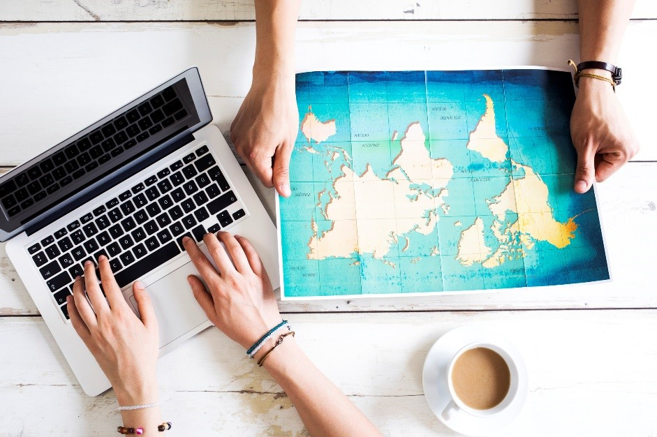 Overhead view of two people at a table with coffee, one is typing on a laptop and one is holding a map of the world.