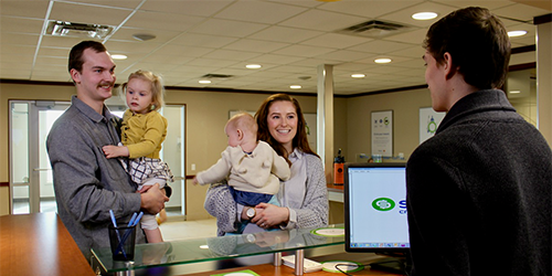 Hannah, her husband and two of their daughters, standing at a teller counter in Servus Credit Union